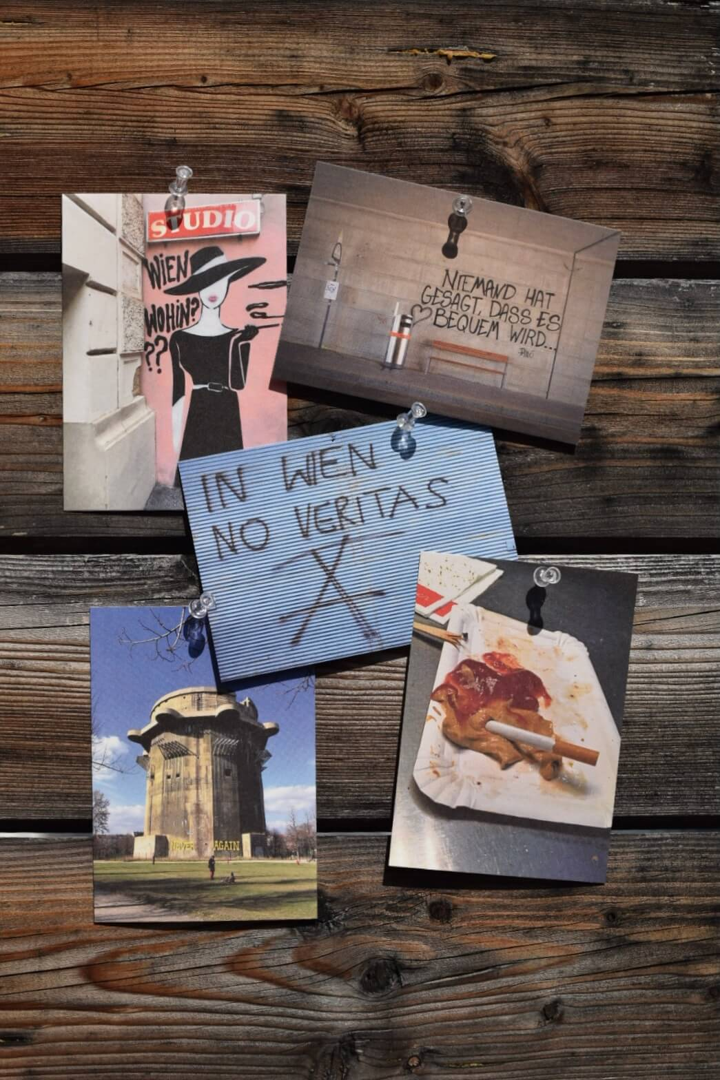 5 bunte Postkarten auf eine Holzwand gepinnt